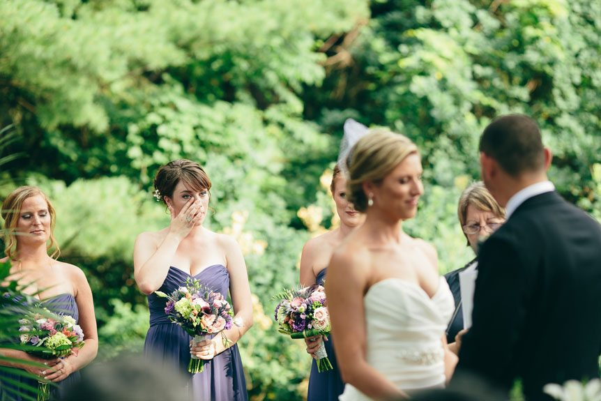 The bride's sister sheds a tear at a Langdon Hall outdoor wedding ceremony as photographed by Toronto wedding photographer.