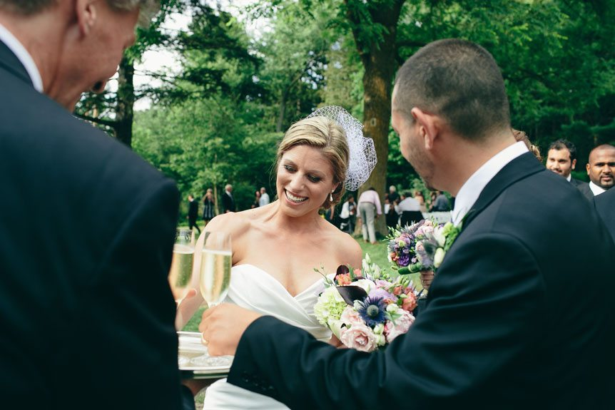 Bride and groom gets a champagne toast from Langdon Hall after their ceremony as photographed by Toronto wedding photographer.