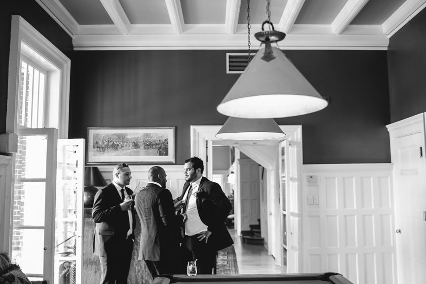 The groomsmen hangs out with each other before a Langdon Hall outdoor wedding as photographed by Toronto wedding photographer.