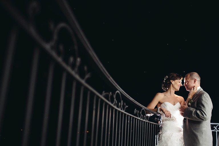 The best Toronto wedding photographer photographs a bride and groom at night at the Cambridge Mill balcony.