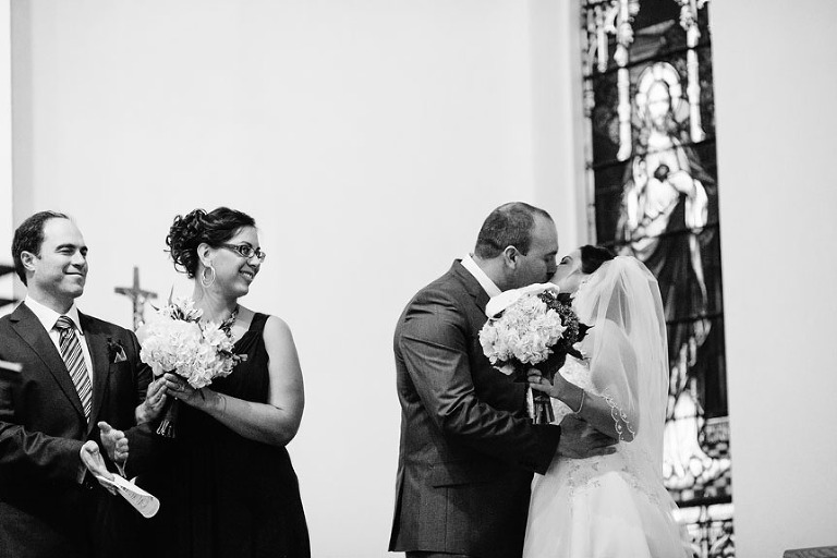 The first kiss of the bride and groom at a Roman Catholic church.