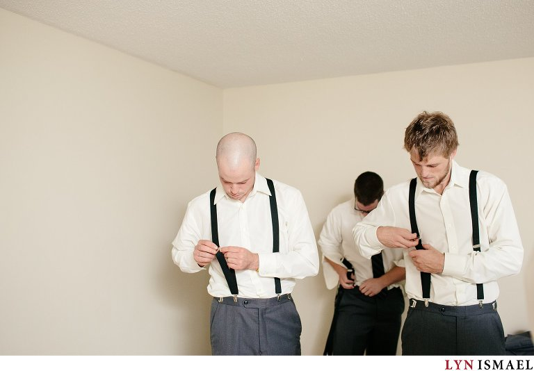 The groom and his groomsmen fix their suspenders.
