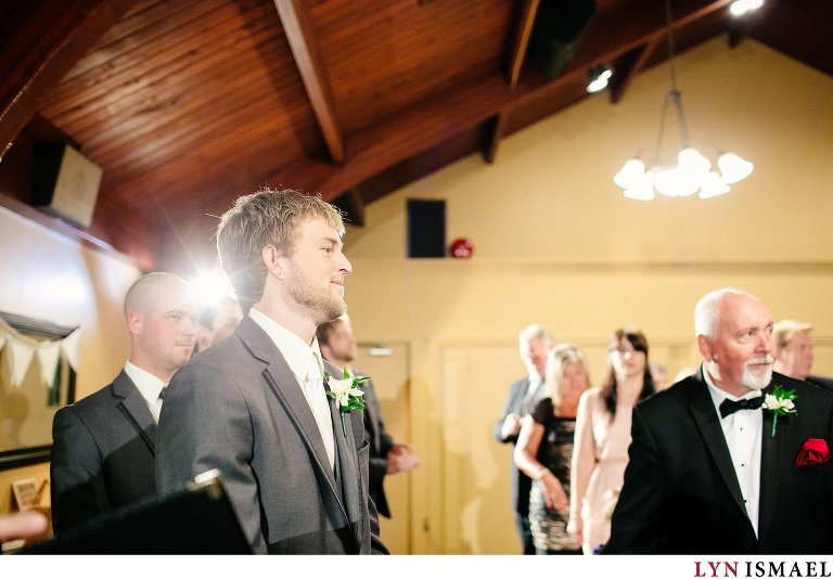The groom watches as his bride walks down the aisle.