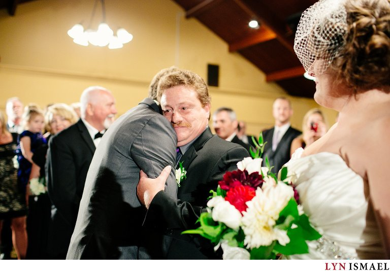 Wedding photojournalist captures the father of the bride hugging the groom as he gives his daughter's hand in marriage.