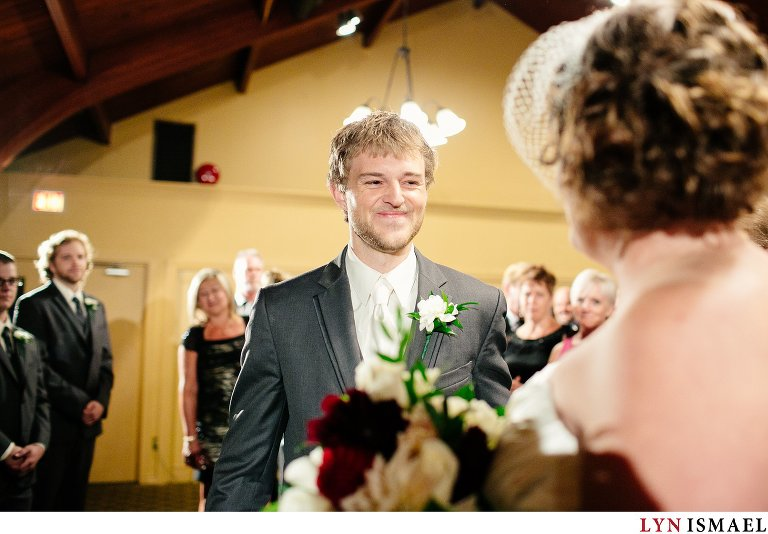 A very happy groom meets his bride at the altar.
