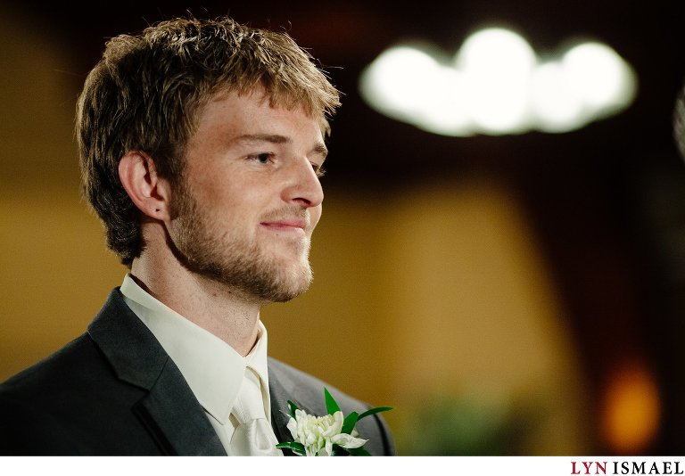 Groom looks at his bride during their wedding ceremony.