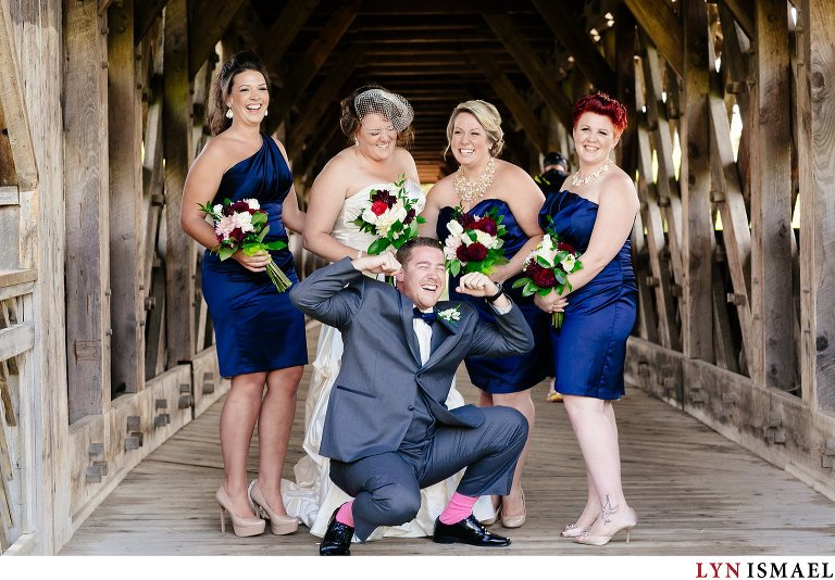 Man of honour with pink socks hanging out with the bride and her bridesmaids.