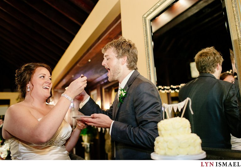 The bride and groom eats their cake.