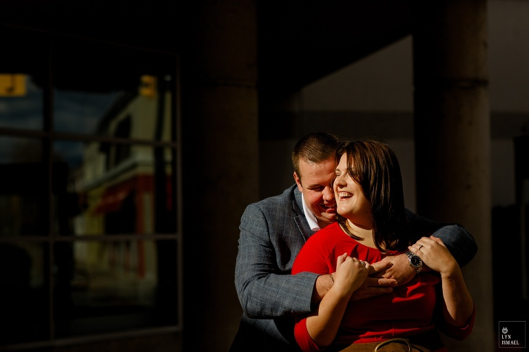 A couple stands in front of the Burlington city hall for their engagement session
