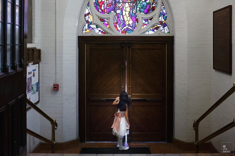 Flower girl takes a peek outside the church