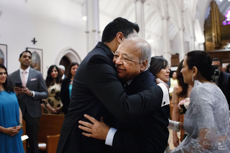 Groom hugs the bride's father at their wedding ceremony at St Basil's Church