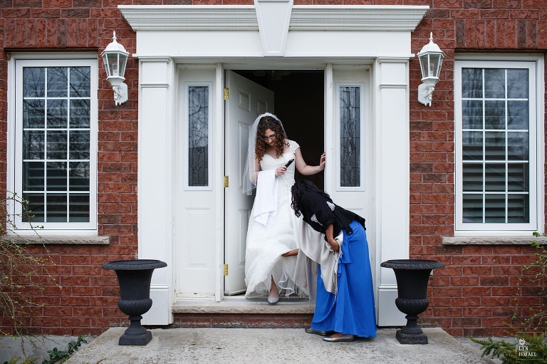 Bride comes out of her parent's house in Wellesley, being helped by her bridesmaid.