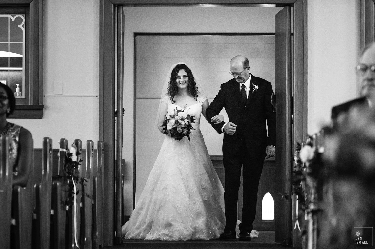Bride walks down the aisle with her father at the Kitchener Mennonite Brethren Church